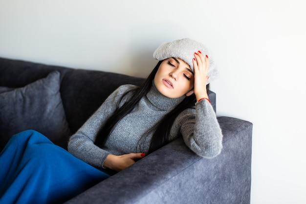 温度を測定した後温度計を見て、ラップトップの作業でベッドの上に座っている灰色のホームウェアで病気の若い女性。病気、フリーランスのコンセプト。
