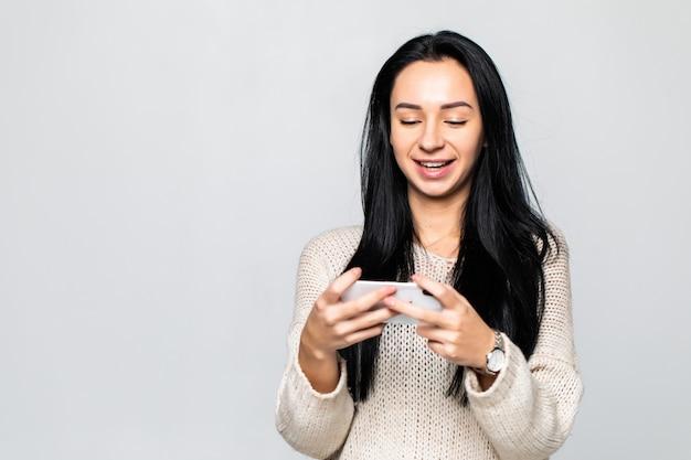 白い壁の壁を越えて分離された携帯電話のポーズで感情的な幸せな陽気な若い女性がゲームをプレイの写真
