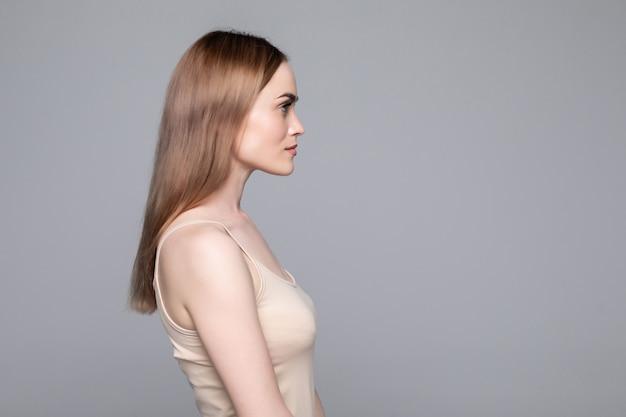 孤立した灰色の壁に立っている若い女性の側面図を閉じる