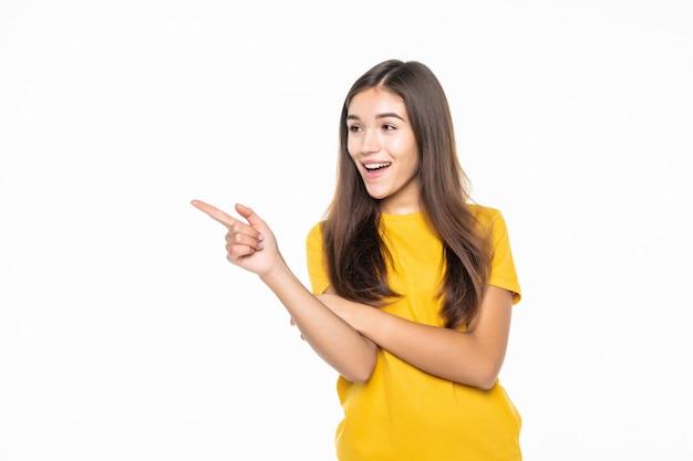 カジュアルな女性の側を指し、白い壁に笑みを浮かべて