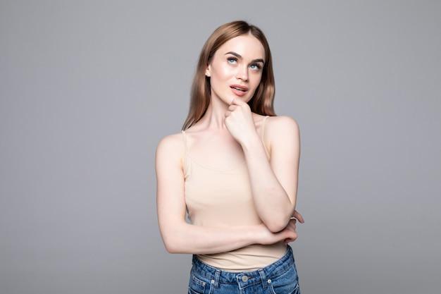 Портрет успешной женщины, глядя в сторону и держа палец в щеку, улыбаясь, изолированных на серую стену