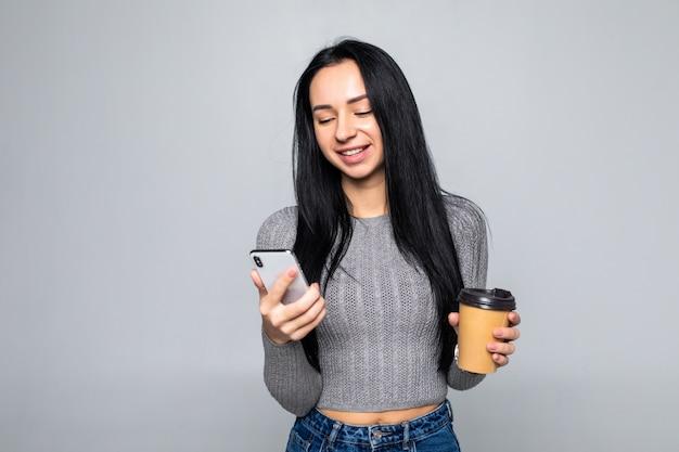 Модные молодая женщина, стоя в чате на мобильном телефоне, держа кружку кофе на вынос в другой руке, изолированные на серую стену