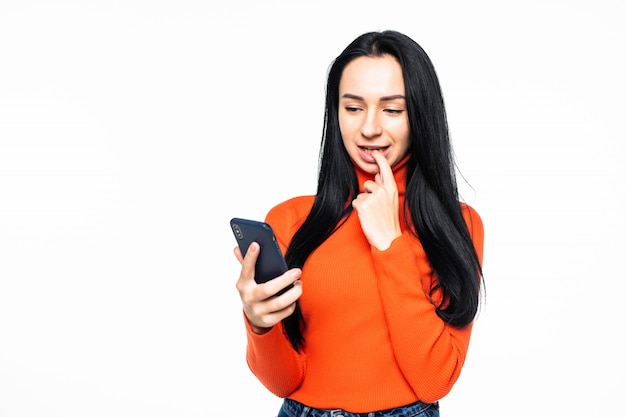 白い壁に分離された電話を使用して若い女性