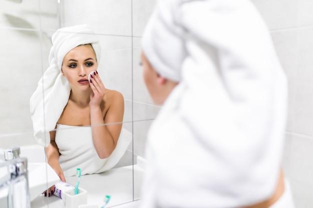 鏡を見て若い魅力的な女性は、バスルームでシャワーを浴びた後、綿パッドで顔を浄化します。スキンケアのコンセプトです。