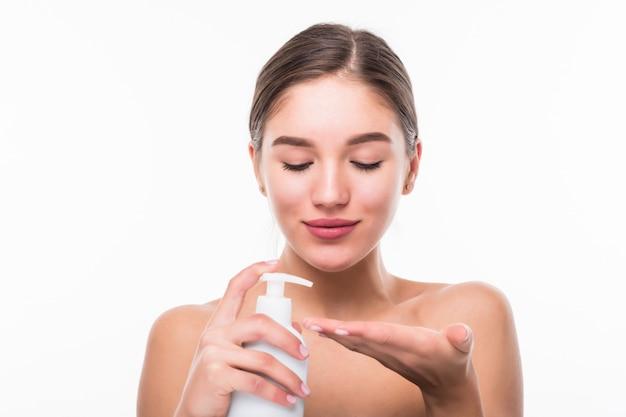 Молодая красивая и естественная женщина, держащая крем бутылку, изолированные на белой стене