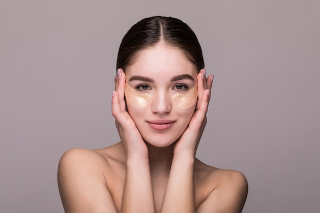 灰色の壁に分離された寺院に触れる目のパッチを持つ若い女性。化粧品、肌ストレスのコンセプト