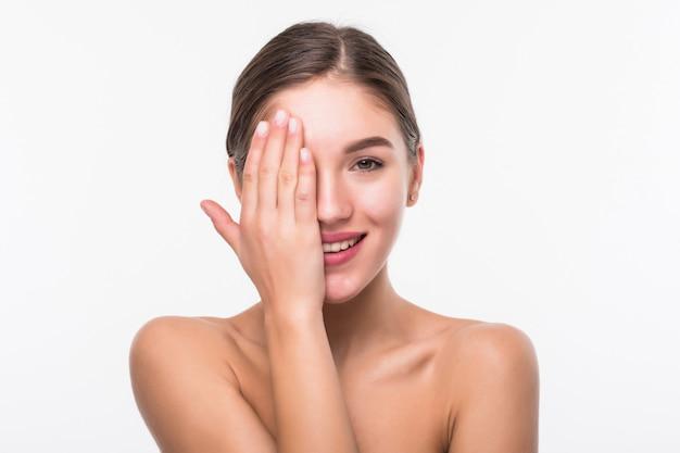 白い壁に分離された清潔でさわやかな肌を持つ若いきれいな女性
