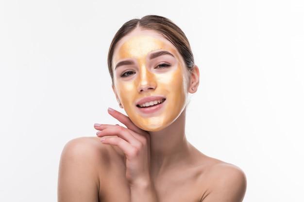 ゴールドマスクを持つ女性。顔の皮膚の化粧品のタッチの顔に黄金のマスクを持つ美しい女性。美容スキンケアと治療