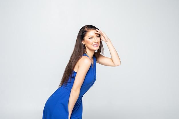 Счастливая игривая молодая женщина в платье стоит и смотрит далеко