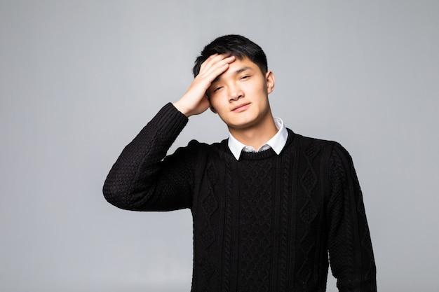 白い壁に分離された頭痛を持っている身に着けている若い中国人男性。ストレスと過労の概念。