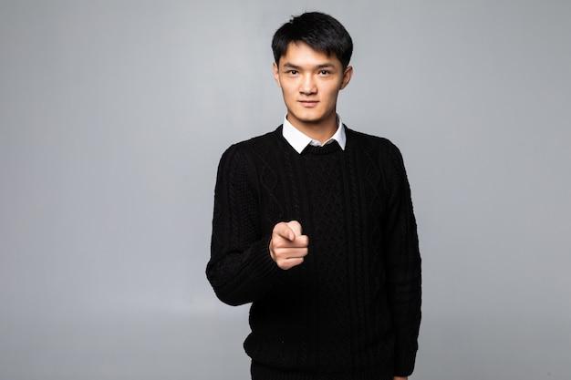 アジアの男の肖像画は孤立した白い壁に指を指す