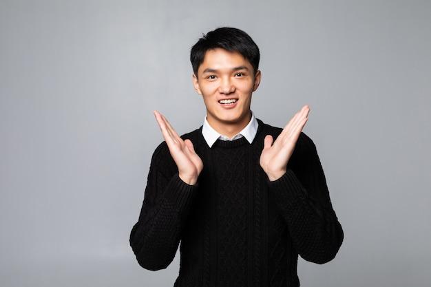 Молодой азиатский китаец удивил человека стоя над изолированной белой стеной