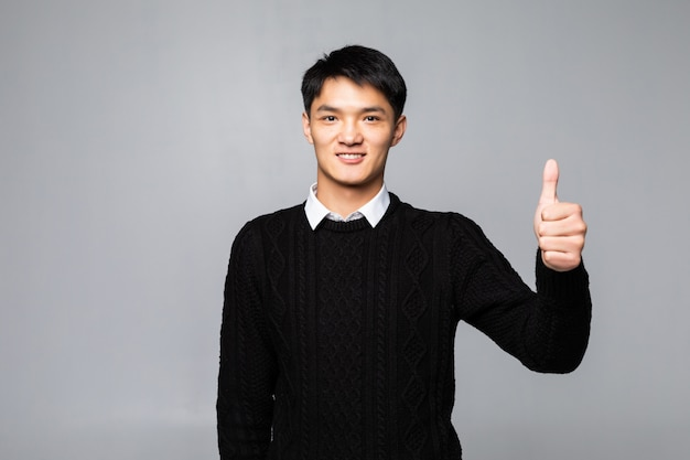 白い壁に身に着けている立っている若い格好良い男。