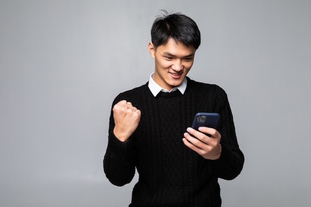 Портрет молодого азиатского человека выглядит счастливым, читая хорошие новости на смартфоне на белой стене