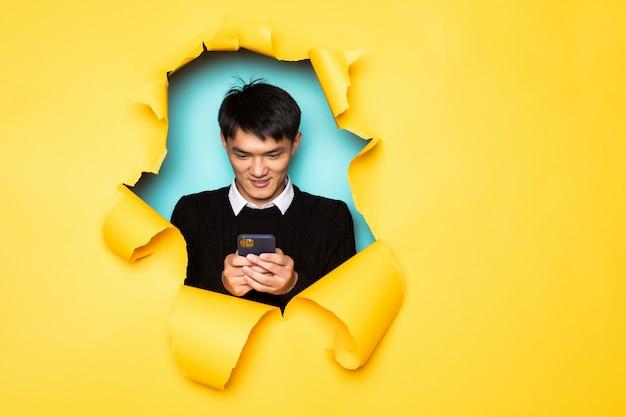若い中国人男性は携帯電話を保持し、引き裂かれた黄色の壁の穴に頭を保ちます。破れた紙の男性の頭。