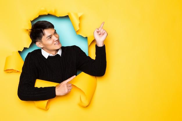 手で先のとがった若い中国人男性は引き裂かれた黄色の壁の穴に頭を保ちます。破れた紙の男性の頭。