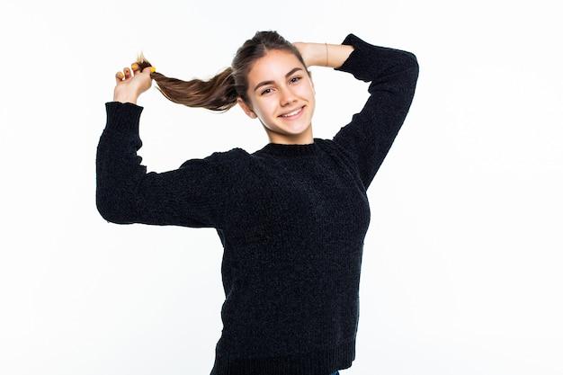 若いかなり十代の少女は白い壁に分離されたポニーテールを作る