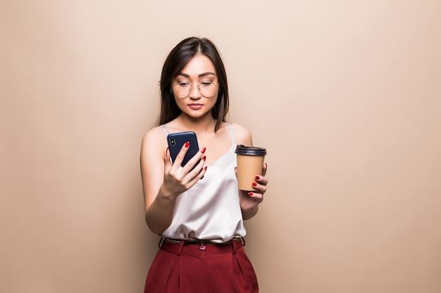 ベージュの壁を越えて行くコーヒーカップを押しながら携帯電話を使用して笑顔のアジア女性の完全な長さの肖像