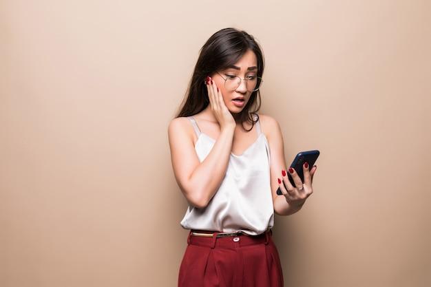 Полнометражный портрет потрясенной азиатской женщины используя мобильный телефон пока держащ чашку кофе для того чтобы пойти изолированный над бежевой стеной