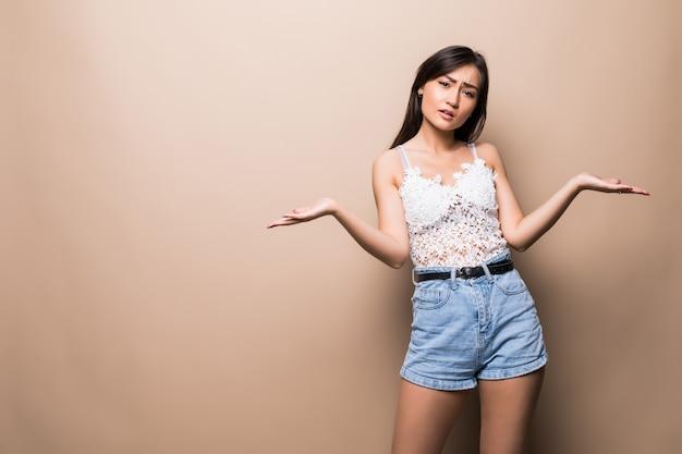 Красивая молодая азиатская женщина представляя ваш очень захватывающий продукт изолированный на бежевой стене