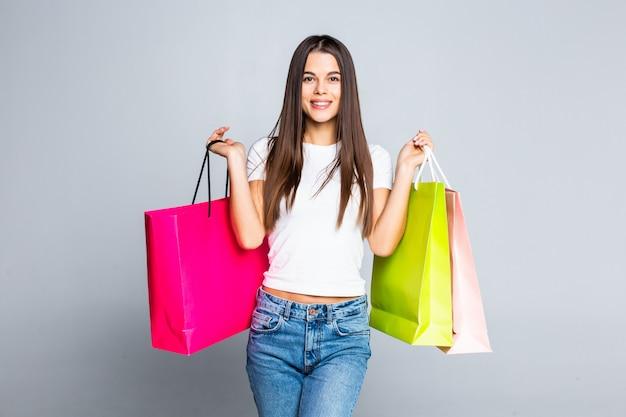 白で隔離されるショッピングバッグを持つ若い女