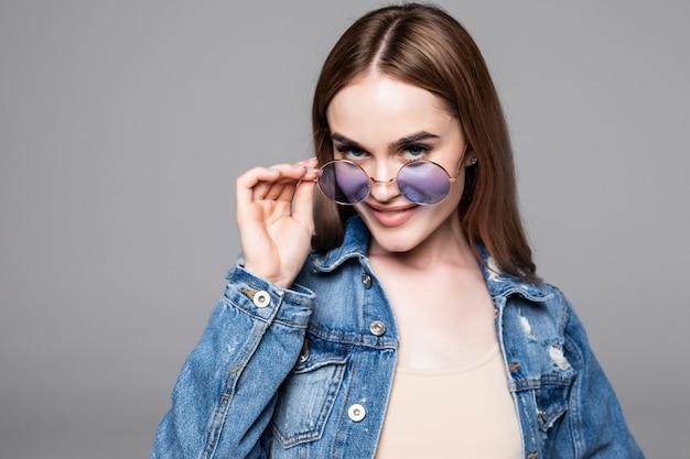 Девушка битника нося пустую серую футболку, джинсы и рюкзак представляя против серой стены