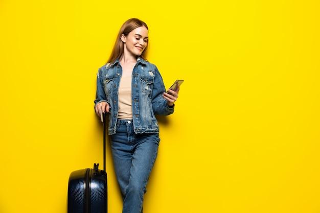 黄色の壁に分離された電話で夏のカジュアルな服でスーツケースを持つ観光女性