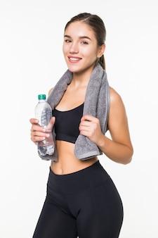 白い壁に対して隔離されるフィットネススポーティな筋肉女飲料水