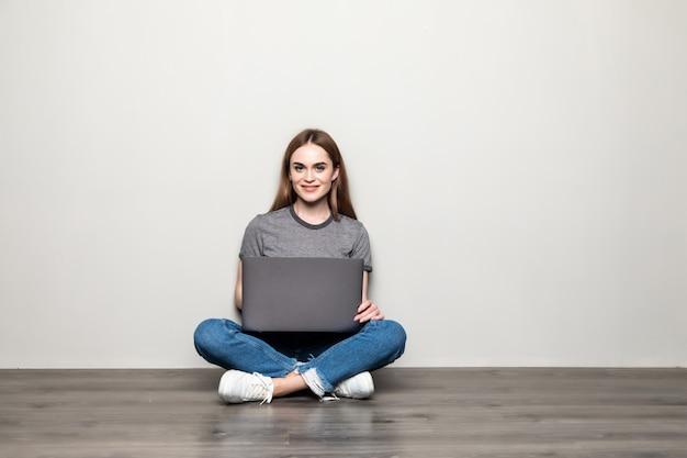 足を組んで、灰色の壁に分離されたコピースペースを離れて床に座ってラップトップコンピューターを保持している魅力的な若い女性
