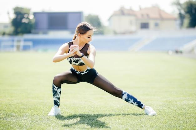 Присев. молодая красавица делает упражнения на стадионе