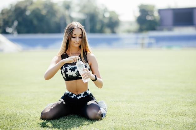 美しい女性は水を飲んで、スタジアムでヘッドフォンで音楽を聴いています。女の子はトレーニング後に休憩しています。