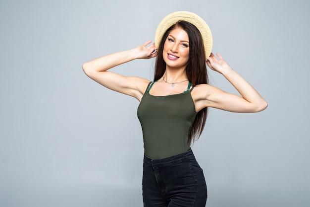 Красивая усмехаясь женщина брюнет в соломенной шляпе изолированной на белизне