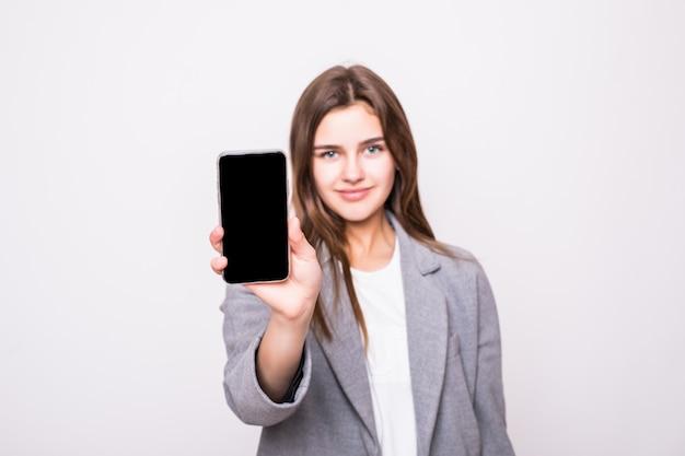 白い背景に空白のスマートフォンの画面を見せて笑ってビジネス女性