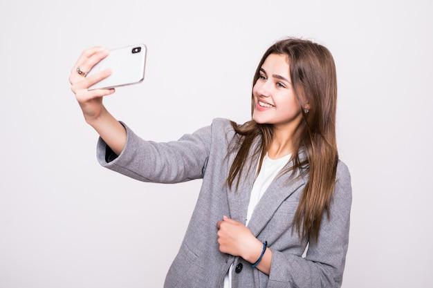 Счастливая молодая девушка фотографировать себя через мобильный телефон, на белом фоне
