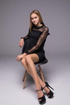 灰色の背景の上に椅子に座って魅力的な笑顔ブルネットの女性