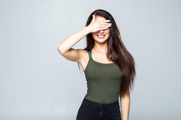 分離された手のひらで彼女の目を覆っている若い女性の肖像画