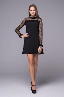 Модель в моде платье позирует на сером фоне