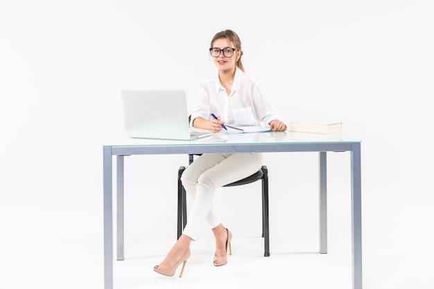 白い背景で隔離のラップトップで机に座っている実業家の肖像画