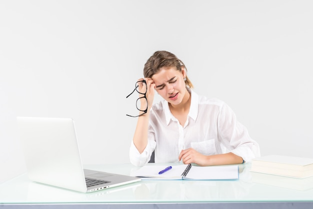 白い背景で隔離のオフィスの机でノートパソコンの前で若い疲れた女性