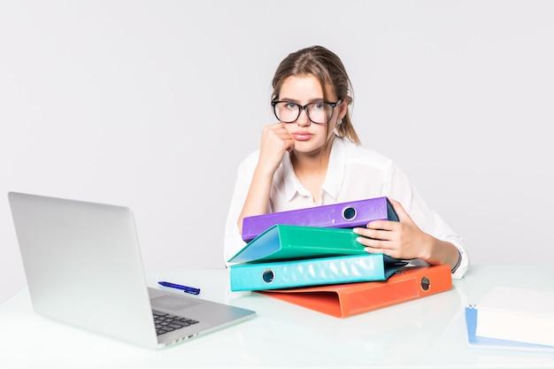 白い背景で隔離のオフィスの机の上のフォルダーを持つ若い疲れたビジネスウーマン