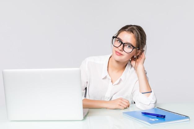 Молодая милая бизнес-леди с тетрадью в столе офиса изолированном на белой предпосылке
