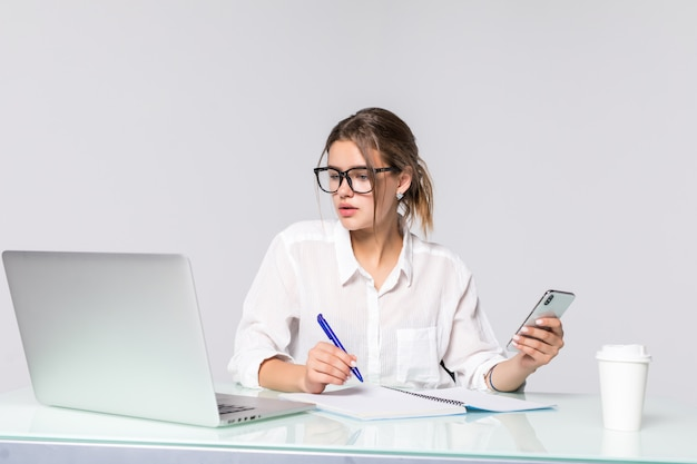白い背景で隔離のオフィスでコンピューターと電話を保持している美しいビジネス女性