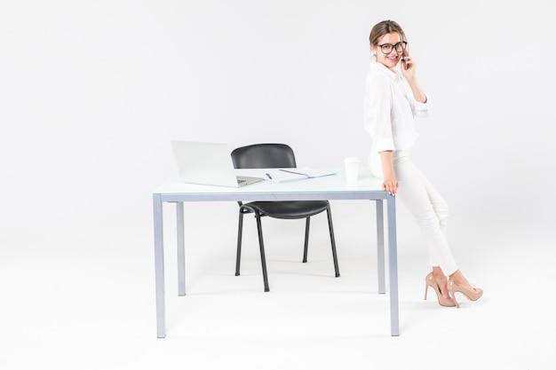 白い背景で隔離のオフィスの机に立っているイライラした重点を置かれた実業家
