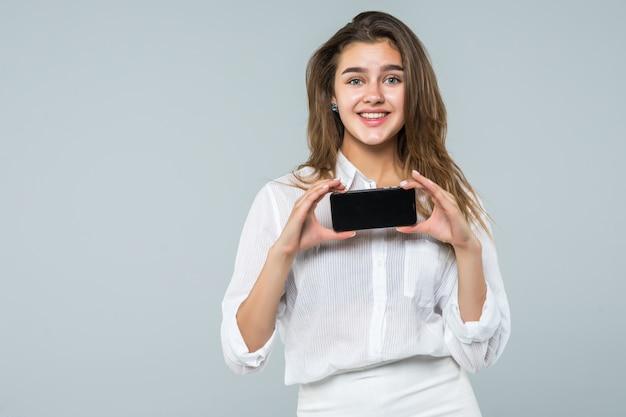 スマートフォンの画面が白い背景で隔離の陽気なかわいい女性の人差し指。