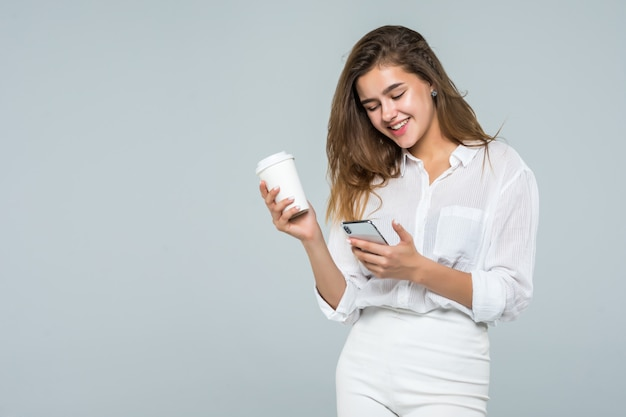 白い背景の上に立って、コーヒーカップを保持しながら携帯電話を使用して幸せな笑顔の女の子の完全な長さの肖像画