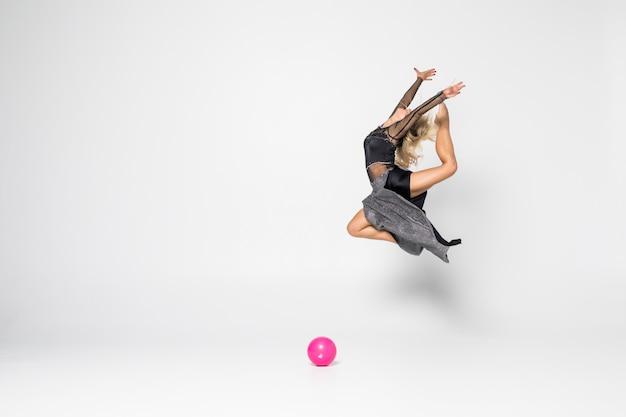 Молодая девушка занимается художественной гимнастикой с мячом