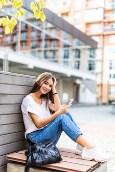 スマートフォンと都市公園のベンチに座っているテキストメッセージを使用して若い女の子