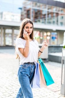 友人に販売について話す。買い物袋を押しながら屋外で立っている間携帯電話で話している美しい若い女性