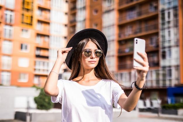 Наружная улица молодой модной женщины, делающей селфи на улице, нося стильную хипстерскую шляпу.