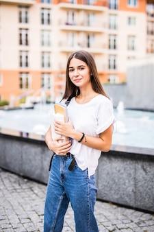 Обратно в школу студент подросток девушка держит книги и записные книжки носить рюкзак. внешний портрет молодой девушки брюнет подростка с длинными волосами. девушка по городу